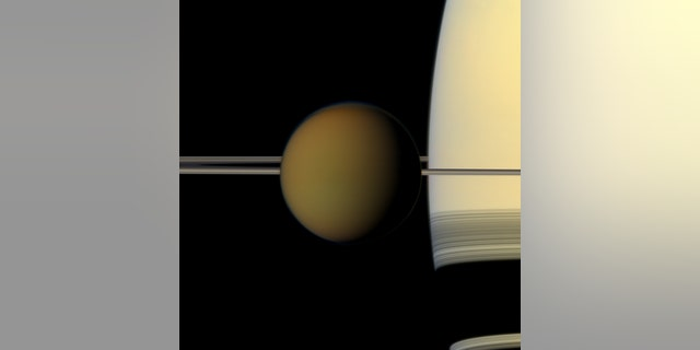 The colorful globe of Titan passes in front of Saturn and its rings in this true-color snapshot from NASA's Cassini spacecraft in 2011. Image credit: NASA/JPL-Caltech/Space Science Institute