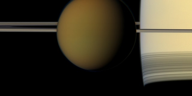 The colorful creation of Titan passes in front of Saturn and a rings in this true-color image from NASA's Cassini booster in 2011. Image credit: NASA/JPL-Caltech/Space Science Institute