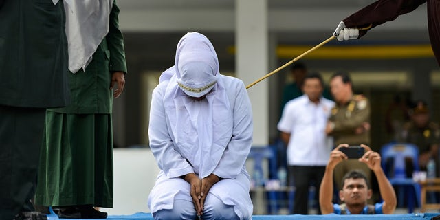 A woman is whipped in public by a member of the Sharia police in Banda Aceh on October 31, 2019, after being caught having an affair with Aceh Ulema Council (MPU) member Mukhlis.