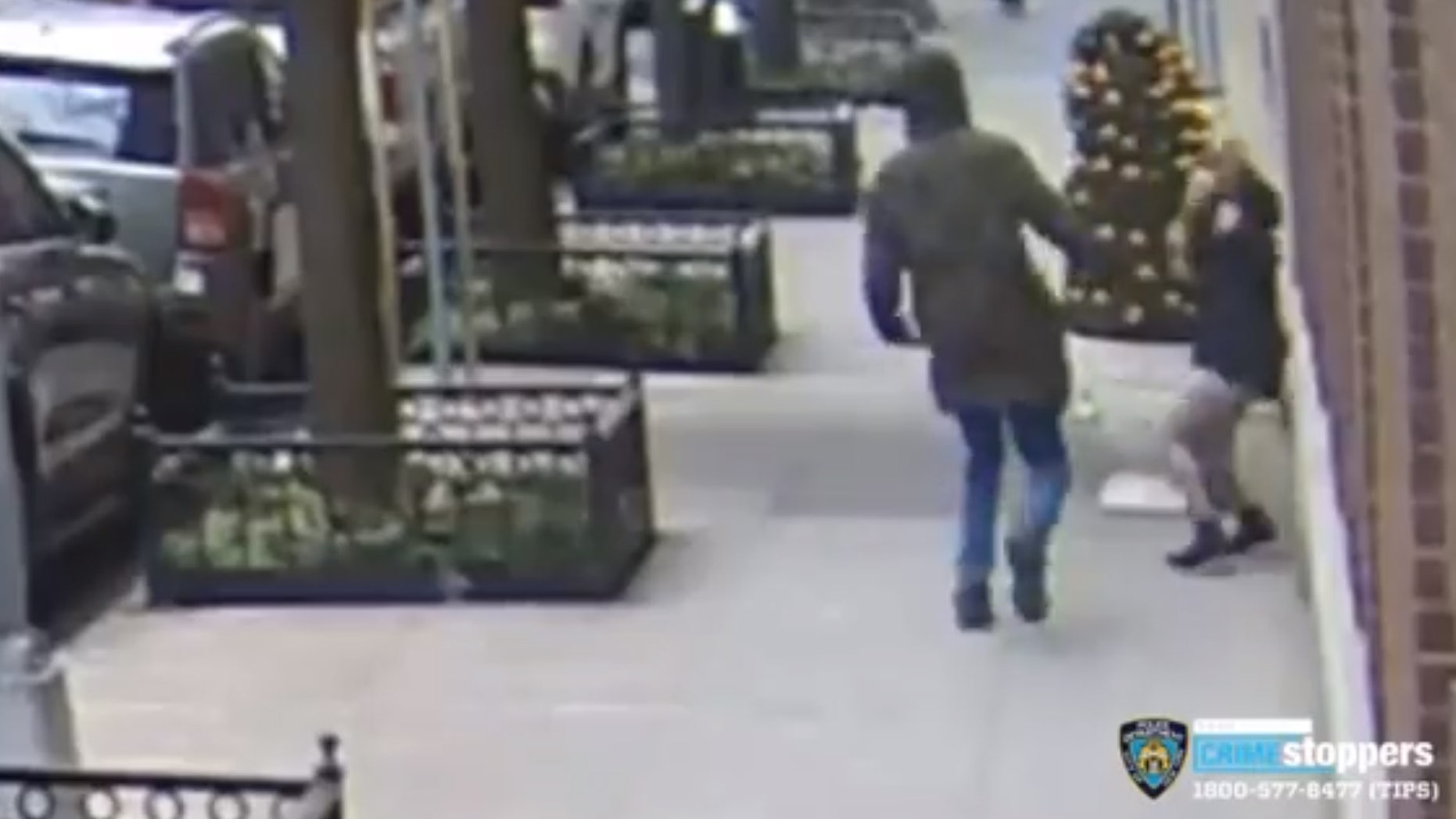 The suspect can be seen swinging at a 21-year-old woman who was on her phone. (NYPD CrimeStoppers)