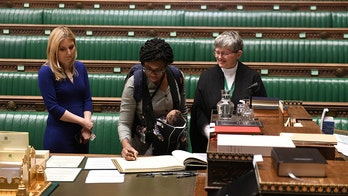 2 UK lawmakers sworn into Parliament while carrying their babies
