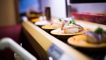 Parents slammed for letting child sit on sushi bar, touch food on conveyor belt