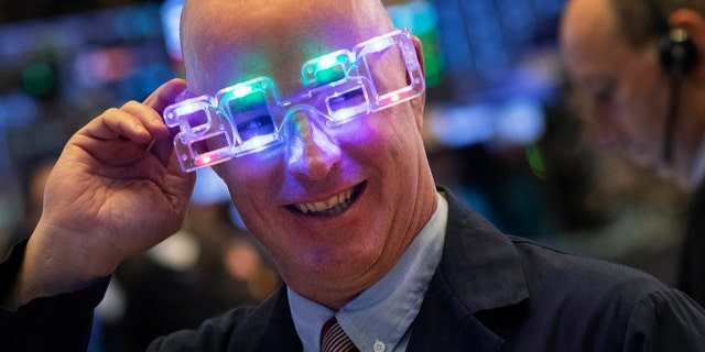 Stock trader John O'Hara tries on his New Year's 2020 party glasses at New York Stock Exchange, Tuesday, Dec. 31, 2019. (Associated Press)