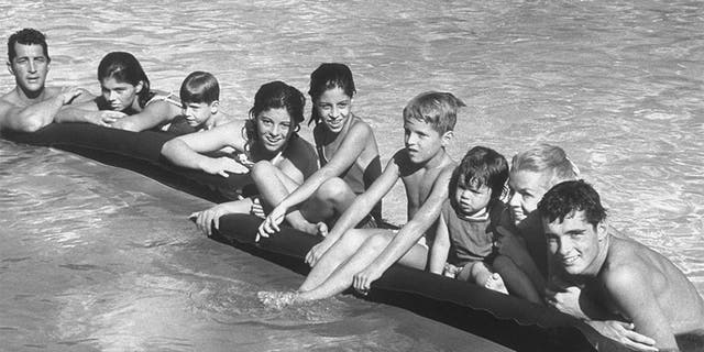 Singer/actor Dean Martin (L) posing w. his 2nd wife Jeanne (2R) & kids incl. (L-R) Claudia,13, Ricci, 5, Barbara Gail, 12, Deana, 10, Dean Paul, 7, Gina, 2, & Craig, 16, as they hang on to air mattresses floating in swimming pool at his Beverly Hills home.