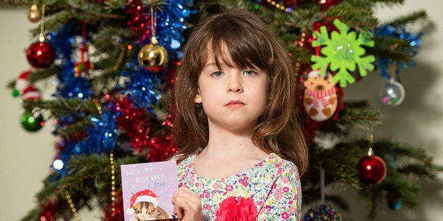 Florence Widdicombe, 6, poses with a Tesco Christmas card from the same pack as a card she found containing a message from a Chinese prisoner. (Dominic Lipinski/PA via AP)