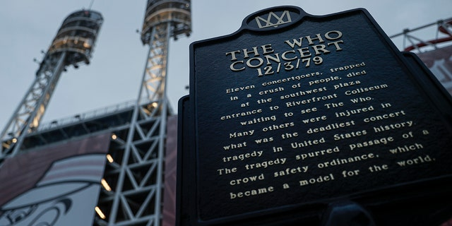 In this Wednesday, Nov. 20, 2019 photo, a commemorative board for eleven concertgoers killed during a 1979 unison stands between Great American Ballpark and Heritage Bank Arena, in Cincinnati. Tragedy 4 decades ago related a British stone rope The Who to a tiny suburban city in Ohio. (AP Photo/John Minchillo)