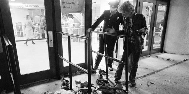 FILE - In this Dec. 3, 1979 record photo, a confidence ensure and an unclear male demeanour during an area where several people were killed as they were held in a surging throng entering Cincinnati's riverfront playhouse for a unison by a British stone rope The Who. (AP Photo/Brian Horton, File)