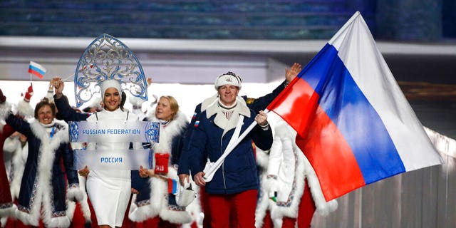 Alexander Zubkov of Russia carries the national flag as he leads the team during the opening ceremony of the 2014 Winter Olympics in Sochi, Russia. Model Irina Shayk, left, is seen carrying the Russian placard.