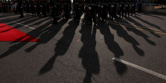 The sun casts the shadows of South Korean soldiers during a welcoming ceremony at Defense Ministry in Seoul.