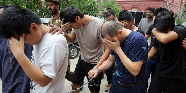 FILE - In this May 11, 2019 file photo, detained Chinese nationals, accused of involvement in a trafficking gang to lure Pakistani women into fake marriages, try to shield their faces while they are escorted by Pakistan's Federal Investigation Agency officers to court in Lahore, Pakistan. (AP Photo/K.M. Chaudary, File)