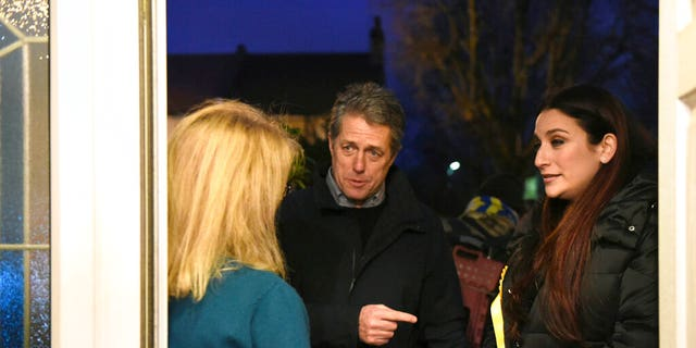 British actor Hugh Grant canvasses with Liberal Democrat Party candidate Luciana Berger, right, while on the general election campaign trail, in London, Sunday Dec. 1, 2019.