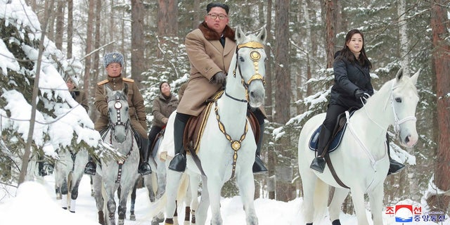 This undated photo provided on Wednesday by the North Korean government shows North Korean leader Kim Jong Un, center, with his wife Ri Sol Ju, right, riding on white horse during his visit to Mount Paektu, North Korea. (Korean Central News Agency/Korea News Service via AP)
