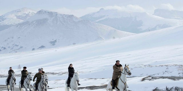 Kim Jong Un, right, and his wife Ri Sol Ju, second from right, riding on white horse during a visit to Mount Paektu, North Korea. (Korean Central News Agency/Korea News Service via AP)