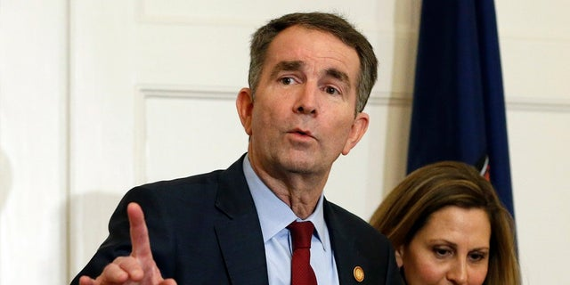 In this Feb. 2, 2019 file photo Virginia Gov. Ralph Northam, left, gestures as his wife, Pam, listens during a press conference in the Governors Mansion at the Capitol in Richmond. A commission Northam tasked with researching racist laws from the state's past recommended Thursday that dozens be repealed in order to purge the state's books of discriminatory language. (AP Photo/Steve Helber, File)