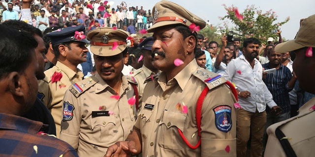 People throw flower petals on the Indian policemen guarding the area where rape accused were shot, in Shadnagar some 50 kilometers or 31 miles from Hyderabad, India, Friday, Dec. 6, 2019. An Indian police official says four men accused of raping and killing a woman in southern India have been fatally shot by police. (AP Photo/Mahesh Kumar A.)