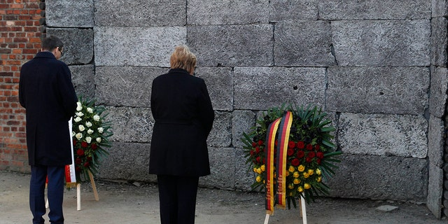 German Chancellor Angela Merkel, left, and Polish Prime Minister Mateusz Morawiecki, right, place flowers at the Death Wall during their visit of the former Nazi death camp of Auschwitz-Birkenau in Oswiecim, Poland.