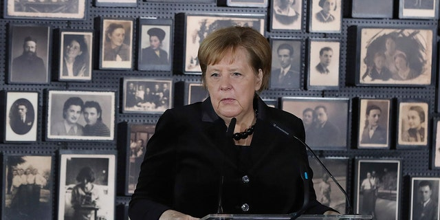 """German Chancellor Angela Merkel speaks in the building of the so-called """"Sauna"""" during her visit at the former Nazi German concentration and extermination camp Auschwitz-Birkenau in Oswiecim, Poland on Friday, Dec. 6, 2019. Merkel attends an event in occasion of the 10th anniversary of the founding of the Auschwitz Foundation."""