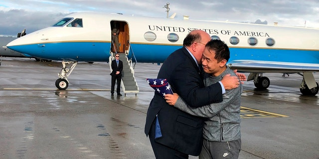 This photo provided by U.S. Embassy Switzerland, Edward McMullen greets Xiyue Wang in Zurich, Switzerland on Saturday, Dec. 7, 2019. In a trade conducted in Zurich, Iranian officials handed over Chinese-American graduate student Xiyue Wang, detained in Tehran since 2016, for scientist Massoud Soleimani, who had faced a federal trial in Georgia. (U.S. Embassy Switzerland via AP)