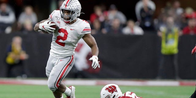Ohio State running back J.K. Dobbins (2) runs past Wisconsin linebacker Jack Sanborn during the second half of the Big Ten championship NCAA college football game Saturday, Dec. 7, 2019, in Indianapolis. (Associated Press)