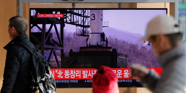 "People watch a TV news program reporting North Korea's announcement with file image at the Seoul Railway Station in Seoul, South Korea, Sunday, Dec. 8, 2019. North Korea said Sunday it carried out a ""very important test"" at its long-range rocket launch site that it reportedly rebuilt after having partially dismantled it after entering denuclearization talks with the United States last year. The part of letters read ""North. Tongchang-ri."" (AP Photo/Lee Jin-man)"