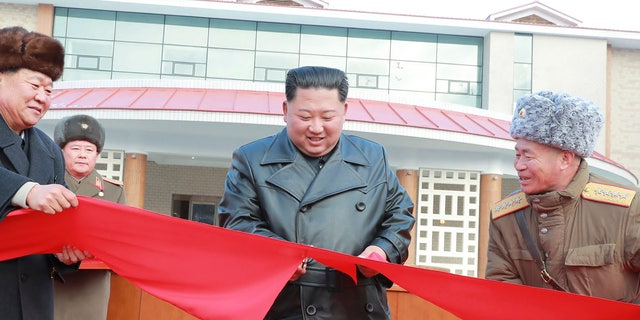 North Korean leader Kim Jong Un, center, cuts the ribbon during a ceremonial opening of the Yangdok Hot Spring Cultural Recreation Center.