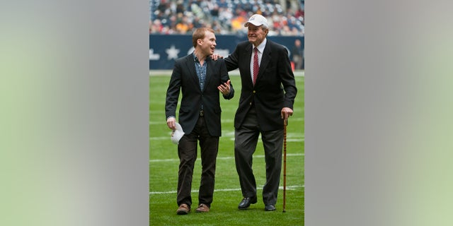 Former President George H. W. Bush leaving the field with the help of Pierce Bush, left, his grandson, before the a college football game in Houston, in 2009. (AP Photo/Dave Einsel, File)