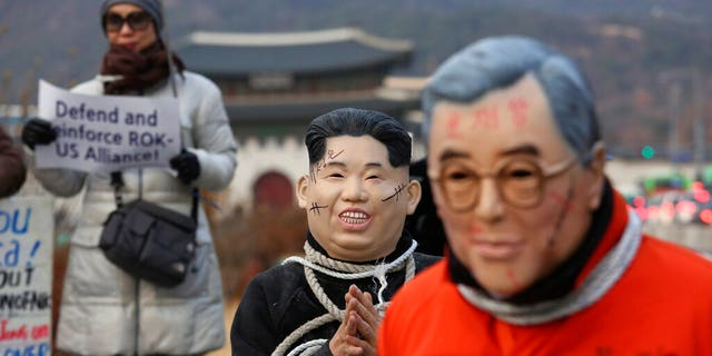 Protesters wear masks of North Korean leader Kim Jong Un and South Korean President Moon Jae-in, right, during a rally to denounce policies of Moon on North Korea near the U.S. embassy in Seoul, South Korea, Friday, Dec. 13, 2019.