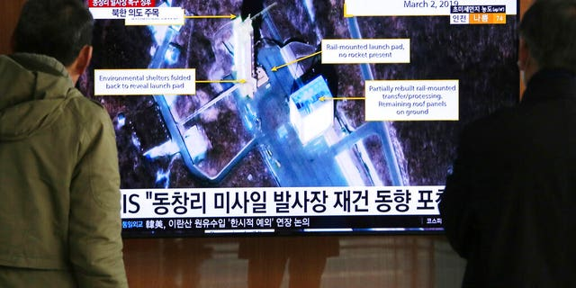 """In this March 6, 2019, file photo, people watch a TV screen showing an image of the Sohae Satellite Launching Station in Tongchang-ri, North Korea, during a news program at the Seoul Railway Station in Seoul, South Korea. North Korea on Saturday, Dec. 14, says it successfully performed another """"crucial test"""" as its long-range rocket launch site that would further strengthen its """"reliable strategic nuclear deterrent.""""The signs read: """" North's Tongchang-ri launch site."""""""