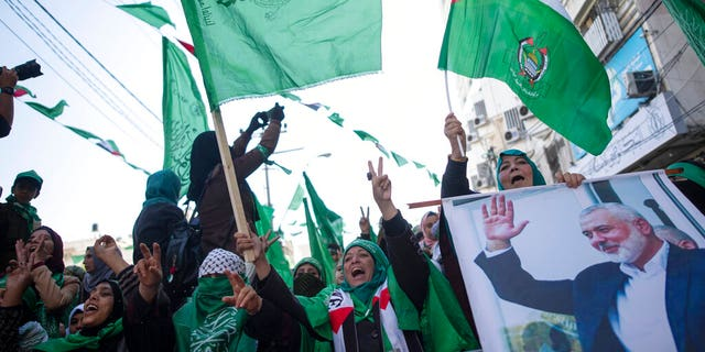 Palestinian women, one holding a picture of Hamas movement chief, Ismail Haniyeh, attend a mass rally marking the 32nd anniversary of the founding of Hamas, an Islamic political party that currently rules in Gaza, Saturday, Dec. 14, 2019, in Gaza city. (AP Photo/Khalil Hamra)