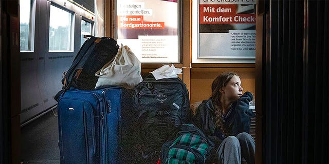 "In this image taken from Twitter feed of Climate activist Greta Thunberg, showing Thunberg sitting on the floor of a train surrounded by bags Saturday Dec. 14, 2019, with the comment ""traveling on overcrowded trains through Germany. And I'm finally on my way home!"" (Twitter @GretaThunberg via AP)"