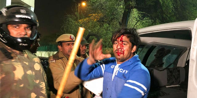 Policemen detaining an injured student outside Jamia Millia Islamia during a protest against Citizenship Amendment Act on Sunday. (AP Photo/Saaliq Sheikh)