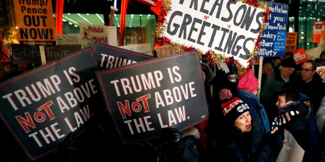 A crowd gathers on Federal Plaza for a protest against President Trump on the eve of a scheduled vote by the U.S. House of Representatives on the two articles of impeachment against the president, Tuesday, Dec. 17, 2019, in Chicago. (Associated Press)