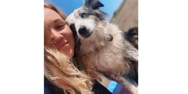 This undated selfie photo provided by Emilie Talermo showing her and her dog Jackson in San Francisco, Calif. Talermo is offering a $7,000 reward for her blue-eyed miniature Australian Shepherd stolen from outside a grocery store. She has hired a plane to fly a banner over the city. (Emilie Talermo via AP)