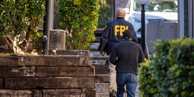 In this Wednesday, Dec. 18, 2019 photo, FBI agents canvas the neighborhood searching for information on Heidi Broussard, a missing Austin, Texas, woman and her infant daughter in South Austin, Texas. Authorities recovered a woman's body and found a child safe in a home on the outskirts of Houston. (Ricardo B. Brazziell/Austin American-Statesman via AP)