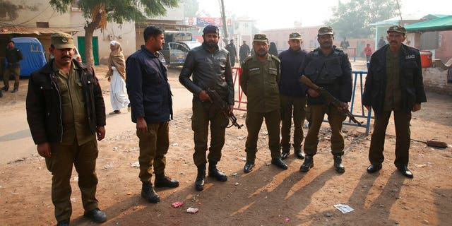 Pakistani police officers stand guard outside Multan jail after a court's decision for a professor facing blasphemy case, in Multan, Pakistan.