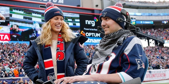In this Dec. 28, 2014, file photo, Julie and Pete Frates smile on the sideline at Gillette Stadium during a birthday ceremony for Pete at an NFL football game between the New England Patriots and the Buffalo Bills in Foxborough, Mass. (AP Photo/Elise Amendola, File)