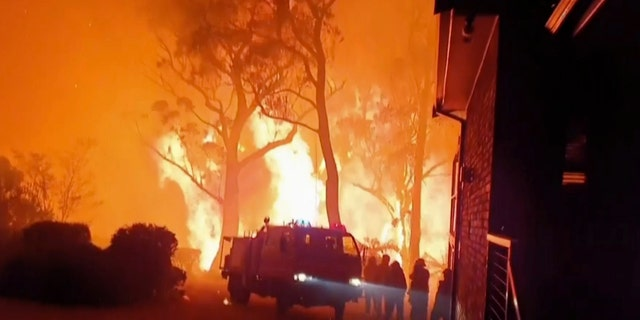 This image made from video taken on Dec. 22, 2019, and provided Dec. 25, 2019, by Ingleside Rural Fire Brigade, shows the wildfire behind an emergency vehicle near property on Hat Hill Road in Blackheath, New South Wales. Australian authorities have warned that the fires in New South Wales could fester for months, causing more angst for exhausted firefighters.(Ingleside Rural Fire Brigade via AP)