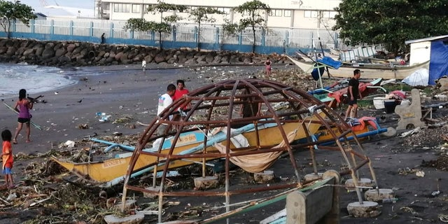 An outrigger and playground equipment damaged by Typhoon Phanfone along the coastline in Ormoc city, central Philippines.