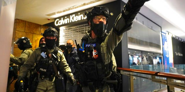 Riot police gesture as they gather at a shopping mall during a demonstration in Hong Kong, Thursday, Dec. 26, 2019. (AP Photo/Vincent Yu)