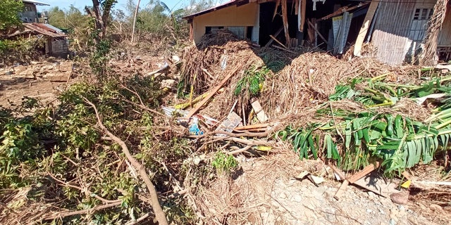 Debris from floods caused by Typhoon Phanfone surrounding a damaged house in Balasan Town, Iloilo province, central Philippines on Thursday.