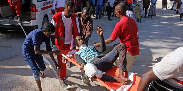 Medical personnel carry a civilian who was wounded in a suicide car bomb attack at checkpoint in Mogadishu, Somalia, Saturday, Dec, 28, 2019. (Associated Press)