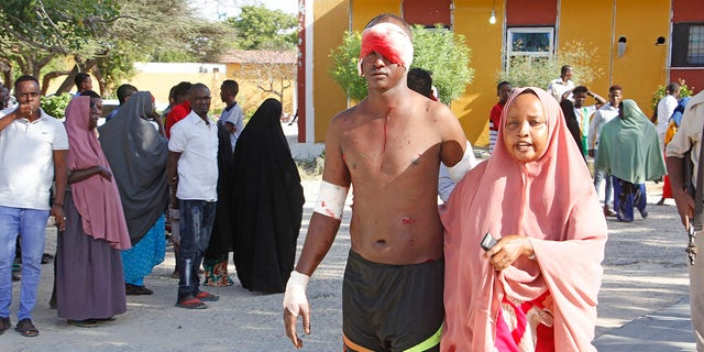 A civilian who was wounded in a suicide car bomb attack is helped at checkpoint in Mogadishu, Somalia, Saturday, Dec, 28, 2019. (Associated Press)