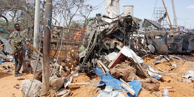 A soldier stands guard near the wreckage of vehicles in Mogadishu after a car bomb in Mogadishu, Somalia, Saturday, Dec. 28, 2019. A truck bomb exploded at a busy security checkpoint in Somalia's capital Saturday morning, authorities said. It was one of the deadliest attacks in Mogadishu in recent memory. (AP Photo/Farah Abdi Warsame)