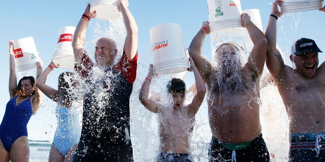 """People take the ice bucket challenge during the last """"Plunge for Pete"""" event on what would have been Pete Frates' 35th birthday, at Good Harbor in Gloucester, Mass., on Dec. 28. (John Blanding/The Boston Globe via AP)"""