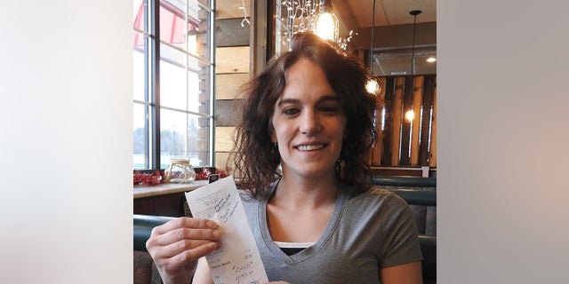 """Server Danielle Franzoni holds a receipt from a customer with a $2,020 tip at the Thunder Bay River Restaurant in Alpena, Mich. The credit card receipt said """"Happy New Year. 2020 Tip Challenge."""" (Julie Riddle/The News via AP)"""