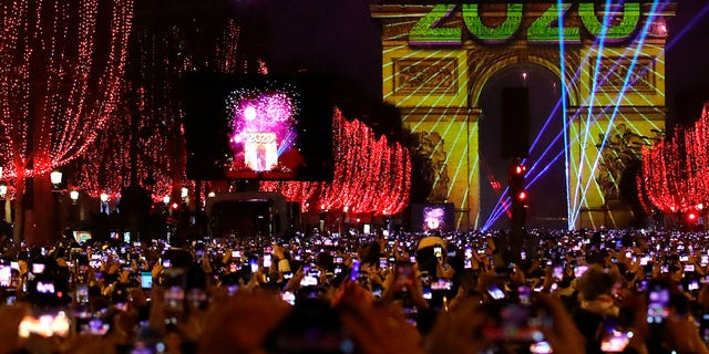 Revellers photograph fireworks over the Arc de Triomphe as they celebrate the New Year on the Champs Elysees, in Paris, France, Wednesday, Jan. 1, 2020. (Associated Press)