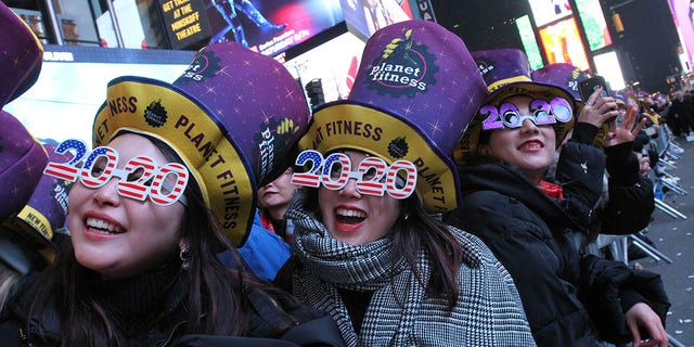 Revelers, including Natsumi Ishikawa, sinistra, and Minori Kondo, second from left, both from Nagoya, Giappone, take part in the New Year's Eve festivities in New York's Times Square, martedì, Dic. 31, 2019. Celebrations this year have been disrupted by the COVID-19 pandemic and the threat of winter storms. (AP Photo/Tina Fineberg)