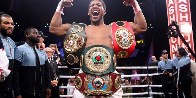 Britain's Anthony Joshua celebrates after beating Andy Ruiz Jr. on points to win their World Heavyweight Championship contest at the Diriyah Arena, Riyadh, Saudi Arabia early Sunday Dec. 8, 2019. (Nick Potts/PA via AP)