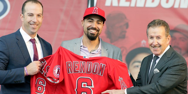 Los Angeles Angels team owner Arte Moreno, right, with general manager Billy Eppler, left, introducing the newest Angel, Anthony Rendon, center, with a jersey during a news conference in Anaheim, Calif., on Saturday. Rendon and the Los Angeles Angels agreed to a $245 million, seven-year contract earlier in the week. (AP Photo/Alex Gallardo)