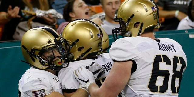 Army running back Connor Slomka (25) celebrates with teammates after making a touchdown against Hawaii during the second half of an NCAA college football game Saturday, Nov. 30, 2019 in Honolulu. (AP Photo/Marco Garcia)